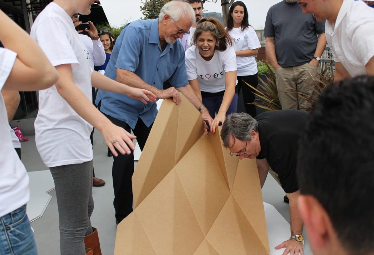 Tina Hovsepian, center, shows the Callison Cares team how to assemble Cardborigami temporary shelters. © 2013 Callison LLC