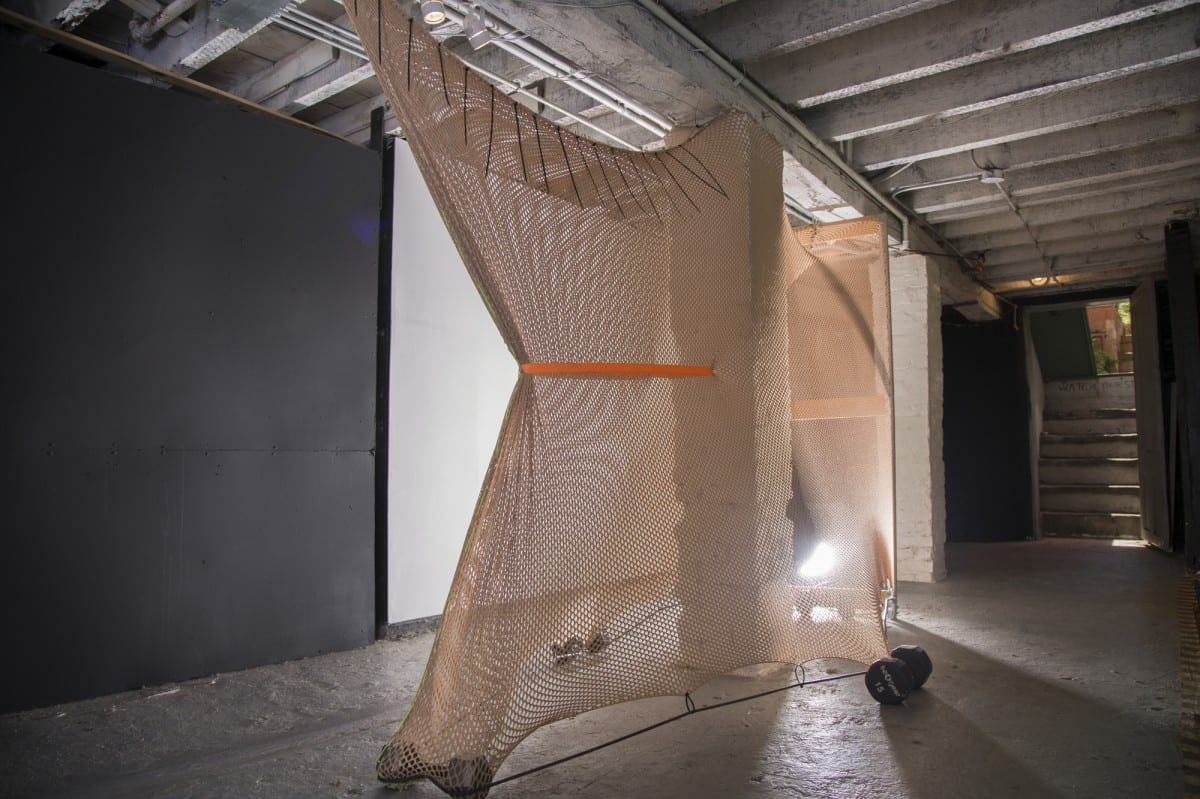 "Leeza Meksin, Landing Gear, Site-specific Installation, Fishnet, wood & steel frame, dumbbells, douche bag, chain, paint, latex tubing, zip ties. 108"" x 72"" x 24"", 2014."
