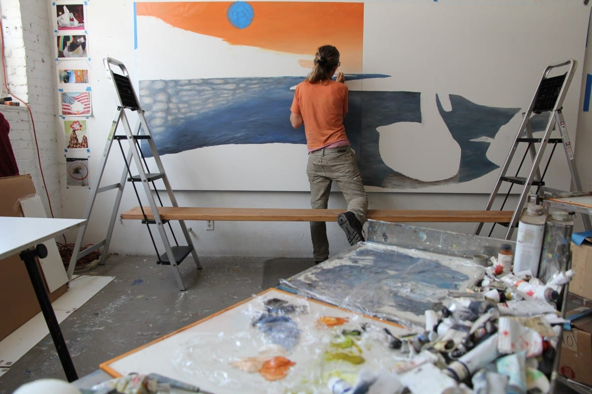 Lisa Adams in the studio painting Borderland.  Photograph by Jayme Odgers.