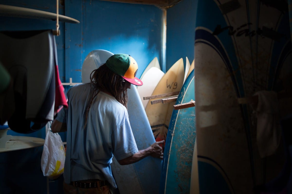 Examining a Seaglass Tuna epoxy alaia from the surfboard racks at the WAVES house. Photo by Forest Woodward.