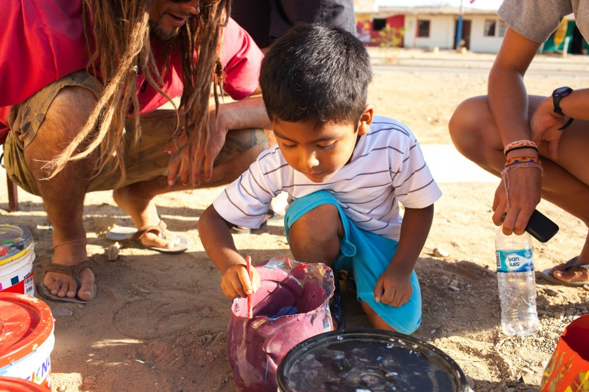 Jared Aufrichtig teaches a Peruvian child to create purple paint by mixing colors during a mural workshop he did in Lobitos. Photo Gary Parker