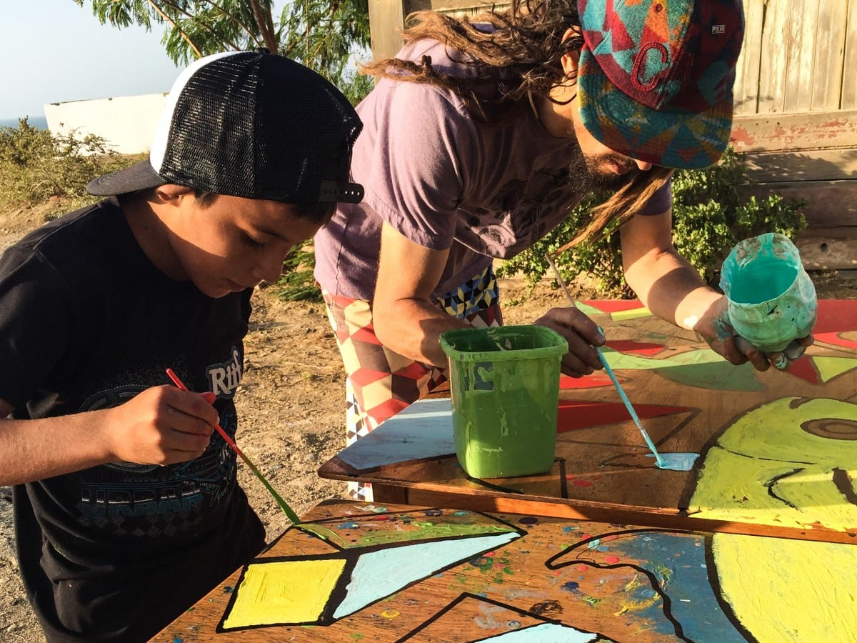 Jared Aufrichtig painting with a local child in Lobitos during one of the creative development workshops he lead in the community.