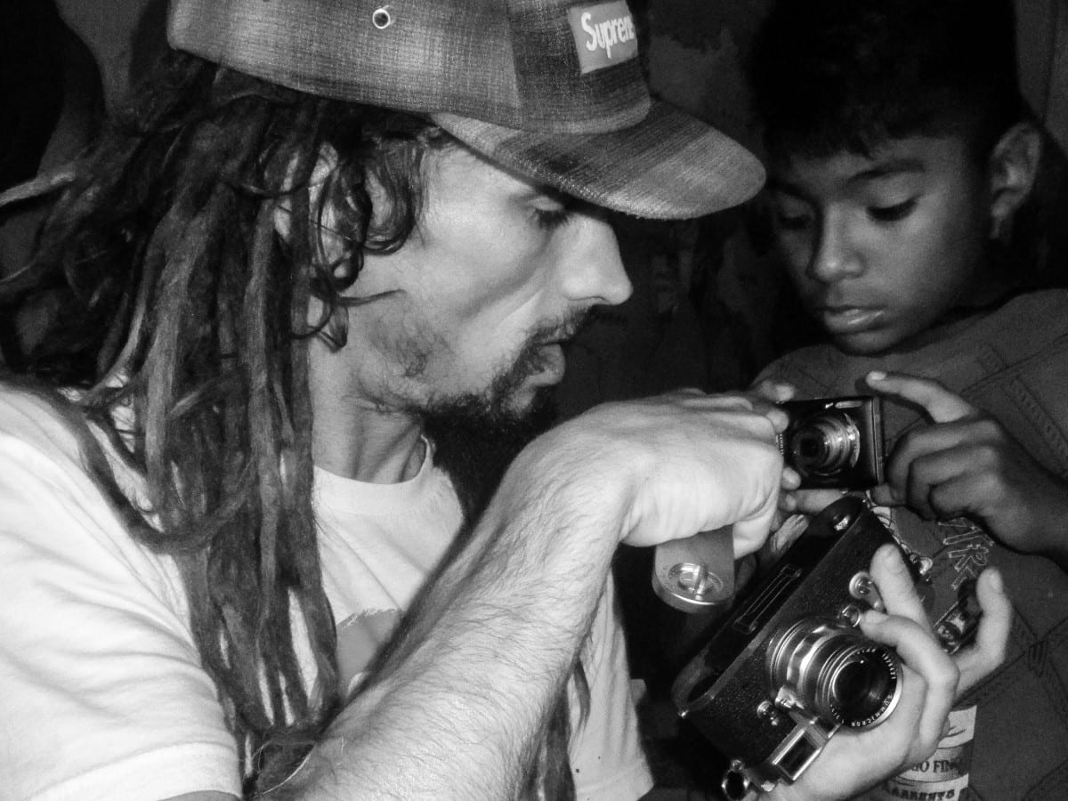 Jared Aufrichtig showing a Peruvian child how  to operate a film camera.  Very different from the digital cameras he is used to. Photo by Martes Photo Class Child.