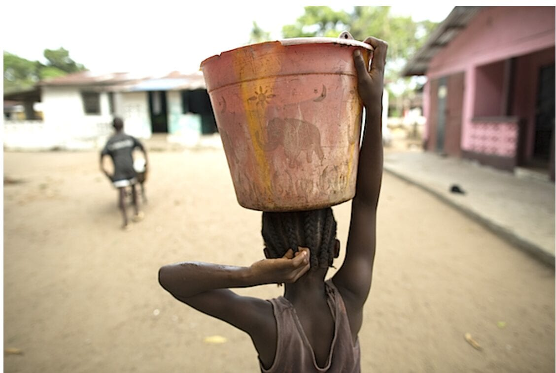 Doing a job many girls must still perform in Guinea, Princess Johnson, 8, carries home a large container of water for her family. ©UNICEF Guinea 2016/ Mohamed Saidou Diallo